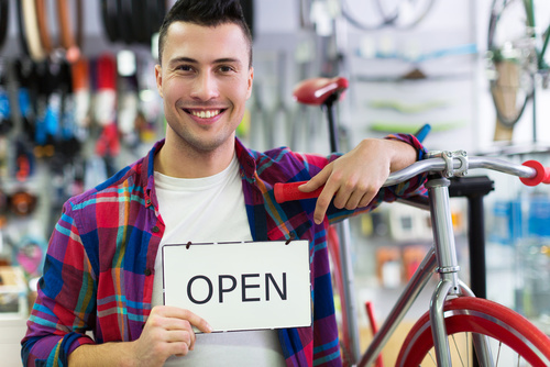 Man in bike shop holding open sign